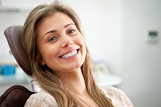Woman smiling in chair at her dental office in West Virginia.